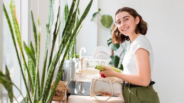 Mulher sorridente segurando vegetais orgânicos