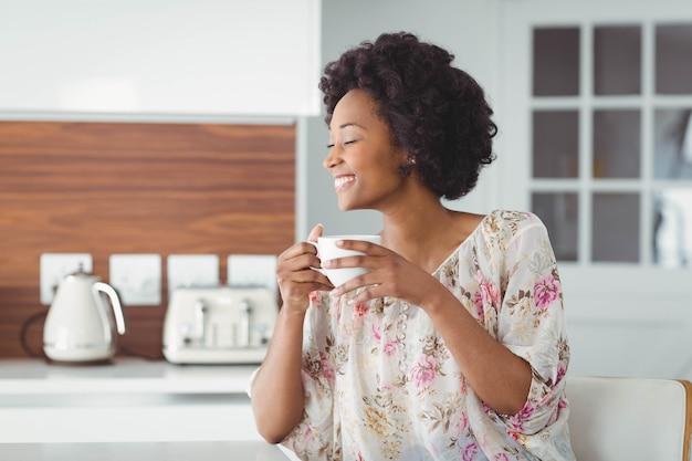 Mulher sorridente segurando xícara branca na cozinha