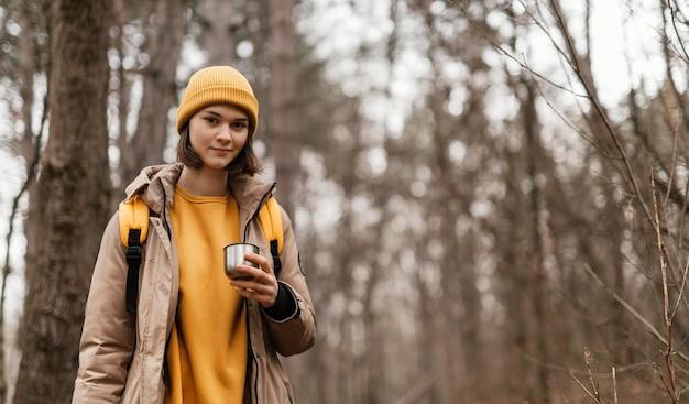 Mulher sorridente segurando xícara na floresta