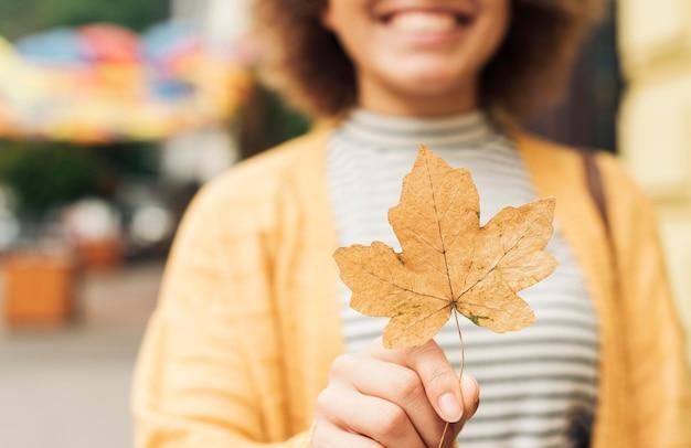 Mulher sorridente sem foco segurando uma folha seca