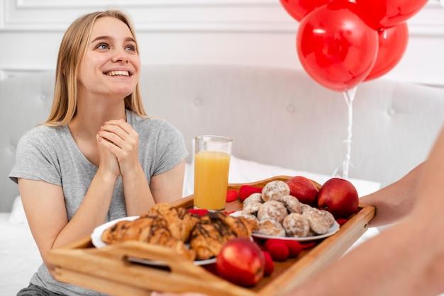 Mulher sorridente, sendo surpreendida com café da manhã na cama