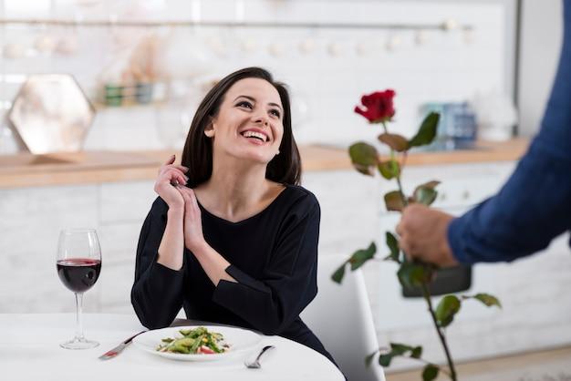 Mulher sorridente, sendo surpreendida pelo marido