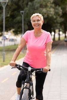 Mulher sorridente sênior andando de bicicleta ao ar livre