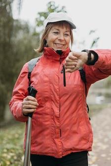 Mulher sorridente sênior olhando para o relógio enquanto caminha ao ar livre Foto Premium