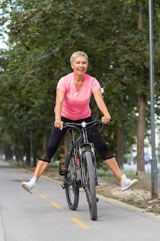 Mulher sorridente sênior se divertindo andando de bicicleta ao ar livre