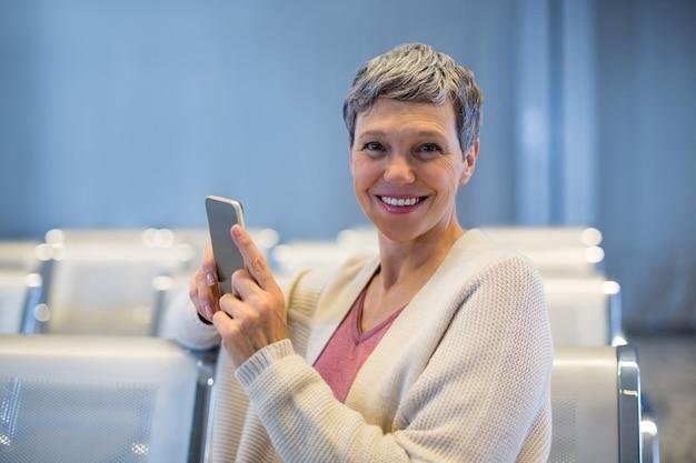 Mulher sorridente, sentada com um celular na sala de espera
