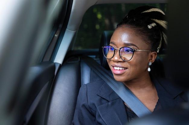 Mulher sorridente sentada dentro de seu carro particular
