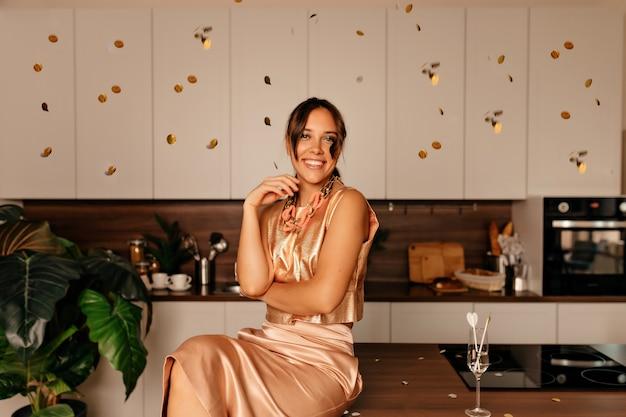 Mulher sorridente, sentada na cozinha com maquiagem brilhante e cabelo ondulado