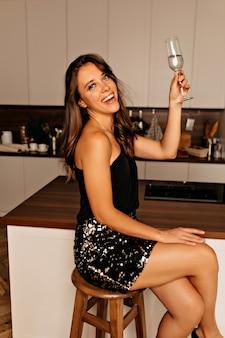 Mulher sorridente, sentada na cozinha com maquiagem brilhante e cabelos ondulados segurando uma taça de vinho