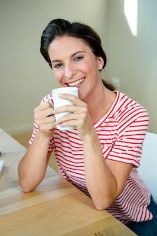 Mulher sorridente, sentada na mesa dela tomando uma xícara de café