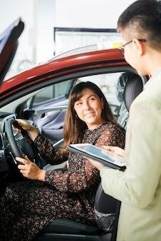 Mulher sorridente, sentada no carro e discutindo alguns detalhes com seguro com o vendedor no salão de automóveis