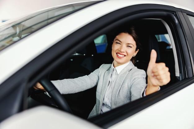 Mulher sorridente sentada no carro que quer comprar e semeando sinal de bom