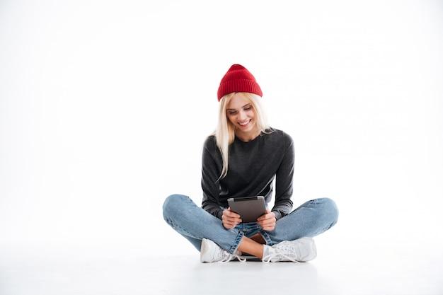 Mulher sorridente, sentada no chão e usando computador tablet