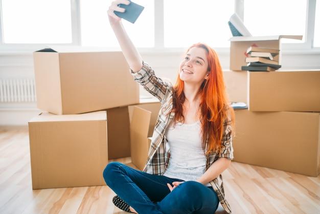 Mulher sorridente, sentada no chão entre caixas de papelão e faz selfie na câmera do celular, inauguração de casa. mudança para nova casa
