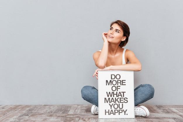 Mulher sorridente, sentada no chão segurando uma prancha com uma frase motivacional isolada em um fundo cinza