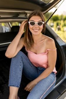 Mulher sorridente sentada no porta-malas de um carro