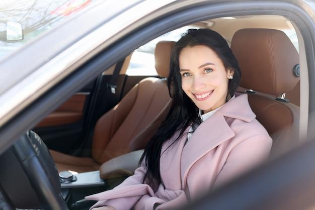 Mulher sorridente sentada no retrato de um carro marrom moderno