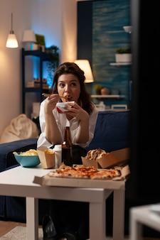 Mulher sorridente, sentada no sofá, comendo saborosa comida chinesa durante entrega de fastfood em casa