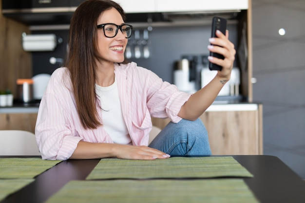 Mulher sorridente, sentada no sofá da cozinha, falando por videochamada namoro online, olhando para o telefone.