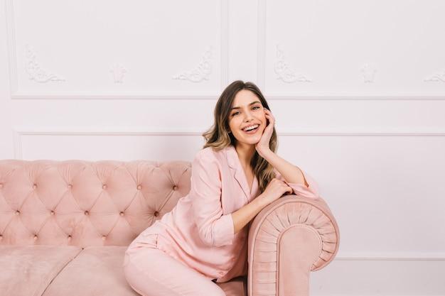 Mulher sorridente, sentada no sofá e apoiando o rosto com a mão
