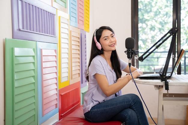 Mulher sorridente, sentada no sofá usando fones de ouvido, olhando para a câmera na frente do microfone