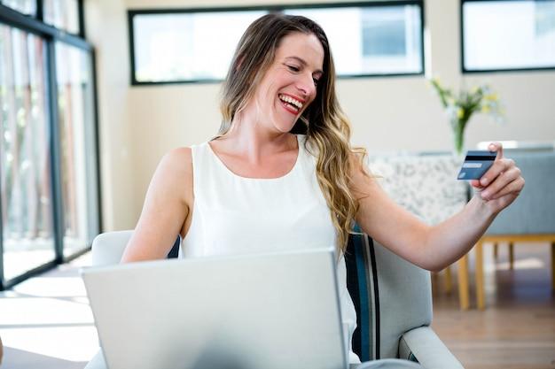 Mulher sorridente, sentada num sofá com seu laptop e cartão de crédito