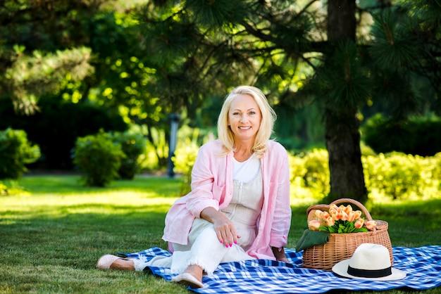 Mulher sorridente, sentada por uma cesta de piquenique