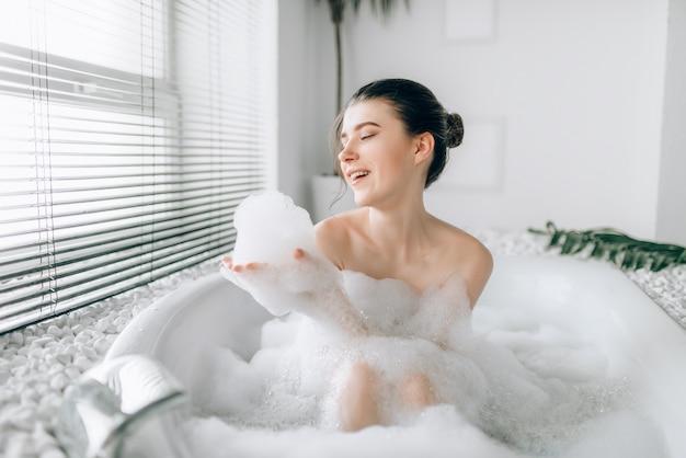 Mulher sorridente, sentado na banheira e brinca com espuma. banheiro luxuoso com janela e decoração de ramo de palmeira