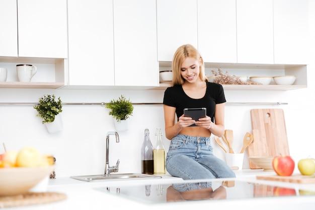 Mulher sorridente, sentado na mesa e usando tablet