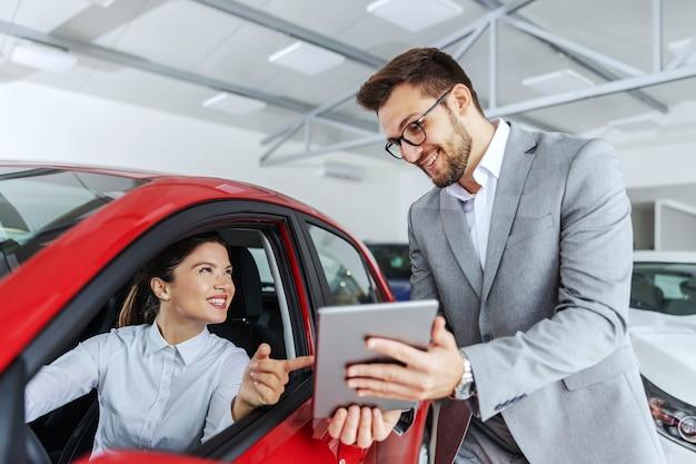 Mulher sorridente, sentado no carro e apontando para o vendedor de carros tablet segurando. ela escolheu o carro certo para ela que viu online. interior do salão do carro.