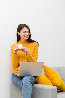 Mulher sorridente, sentado no sofá ao lado do laptop e segurando a xícara de café