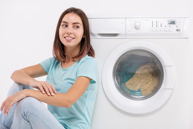 Mulher sorridente, sentado perto da máquina de lavar roupa