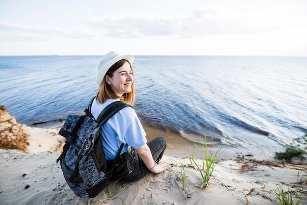 Mulher sorridente, sentando, perto, mar Foto gratuita