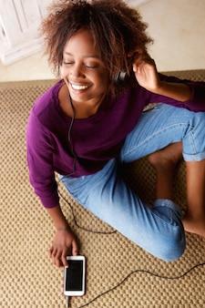 Mulher sorridente, sentar chão, escutar música, ligado, fones