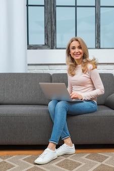 Mulher sorridente, sentar sofá, com, laptop, ligado, dela, colo, olhando câmera