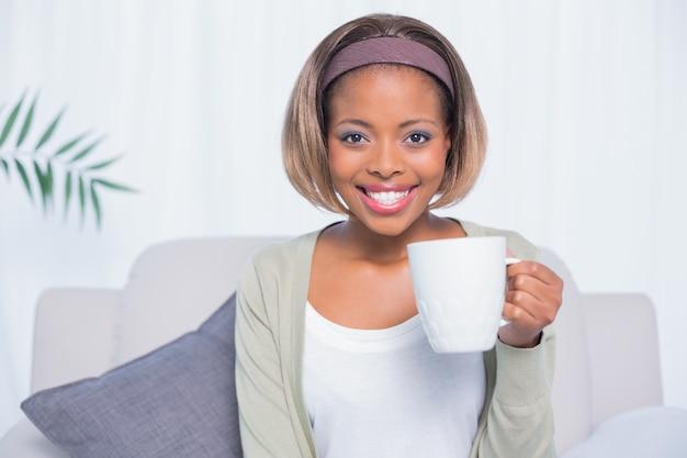 Mulher sorridente, sentar sofá, segurando, assalte café