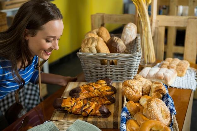 Mulher sorridente sentindo o cheiro de um salgadinho de padaria no balcão