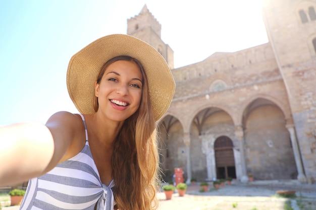 Mulher sorridente tira uma selfie com a catedral de cefalu na sicília, itália