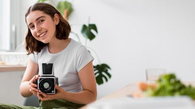 Mulher sorridente tirando fotos com uma câmera profissional