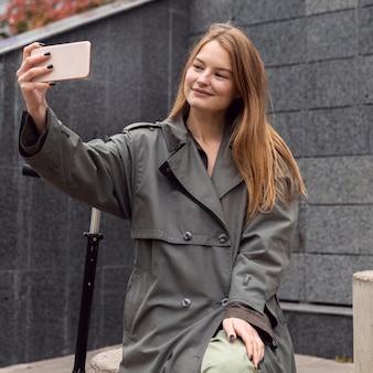 Mulher sorridente tirando selfie ao lado de uma scooter elétrica
