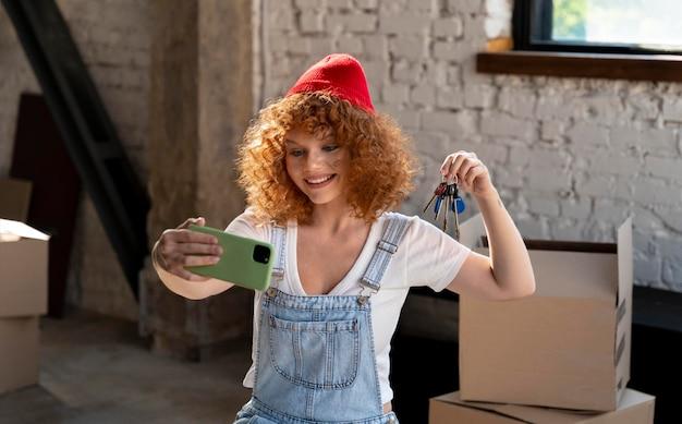 Mulher sorridente tirando selfie com smartphone em sua nova casa com chaves