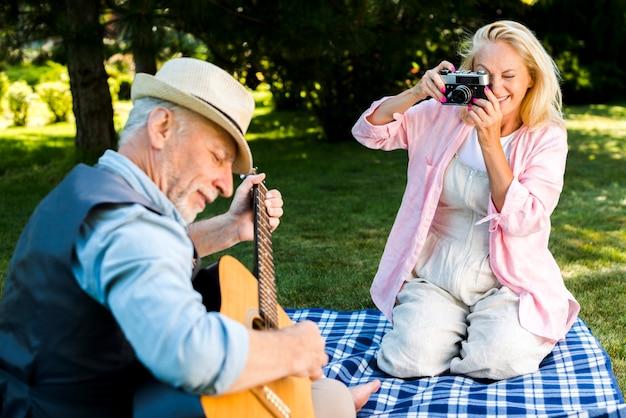 Mulher sorridente, tirando uma foto para um homem com uma guitarra