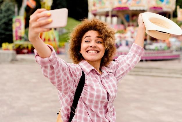 Mulher sorridente tirando uma selfie em um parque de diversões