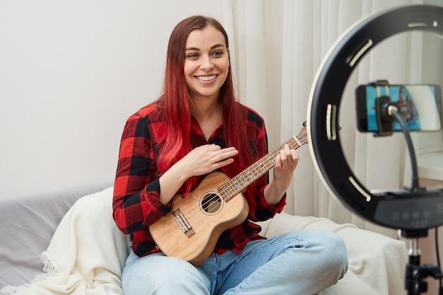 Mulher sorridente tocando ukulele gravando na câmera do telefone, o músico faz um show ao vivo em casa