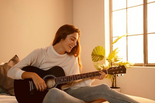 Mulher sorridente tocando violão em casa na cama