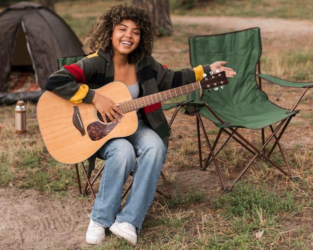 Mulher sorridente tocando violão enquanto acampa ao ar livre