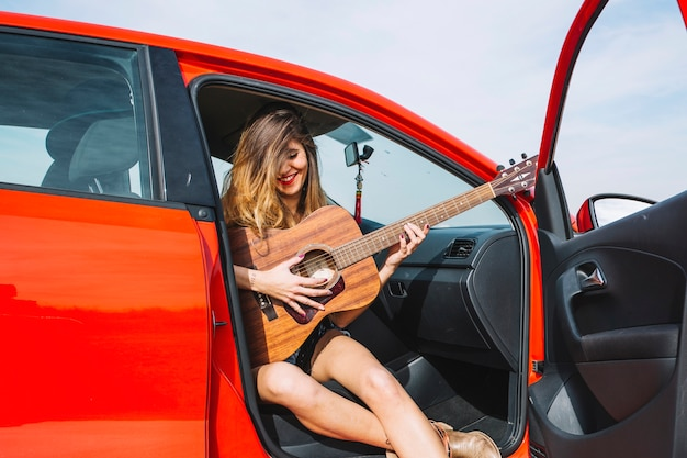 Mulher sorridente tocando violão no carro
