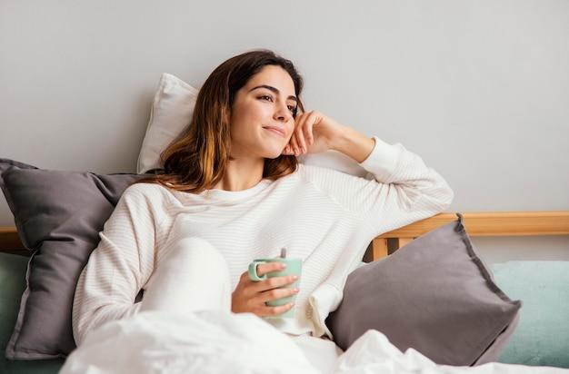 Mulher sorridente tomando café na cama