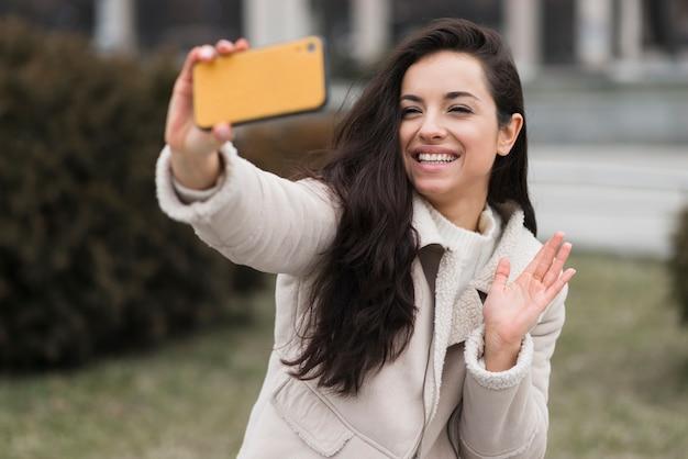 Mulher sorridente tomando selfie ao ar livre
