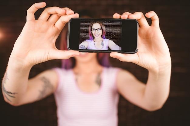 Mulher sorridente tomando selfie do telefone móvel